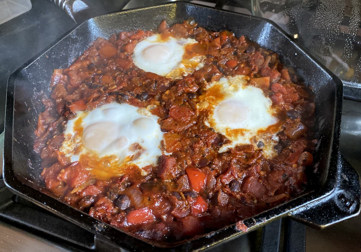 Mexican bean shakshuka with three eggs cooking in a cast iron pan
